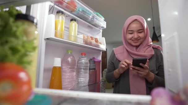 woman using her smartphone to buy groceries while open her fridge at home