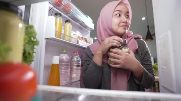 muslim woman fail her diet by eating sweets snack in the fridge