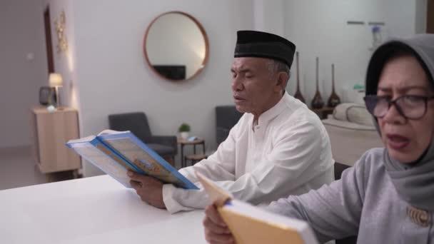 Muslimský starší muž učí ženu číst Korán nebo Korán v obývacím pokoji