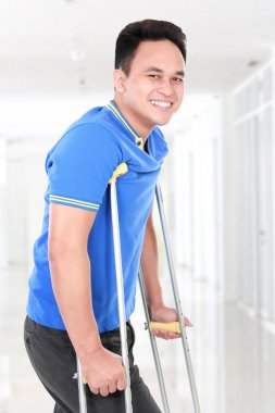 Injured young man walking with the help of crutches