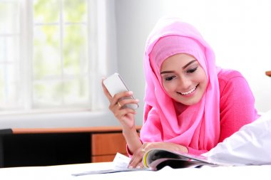 young muslim woman reading a magazine on bed