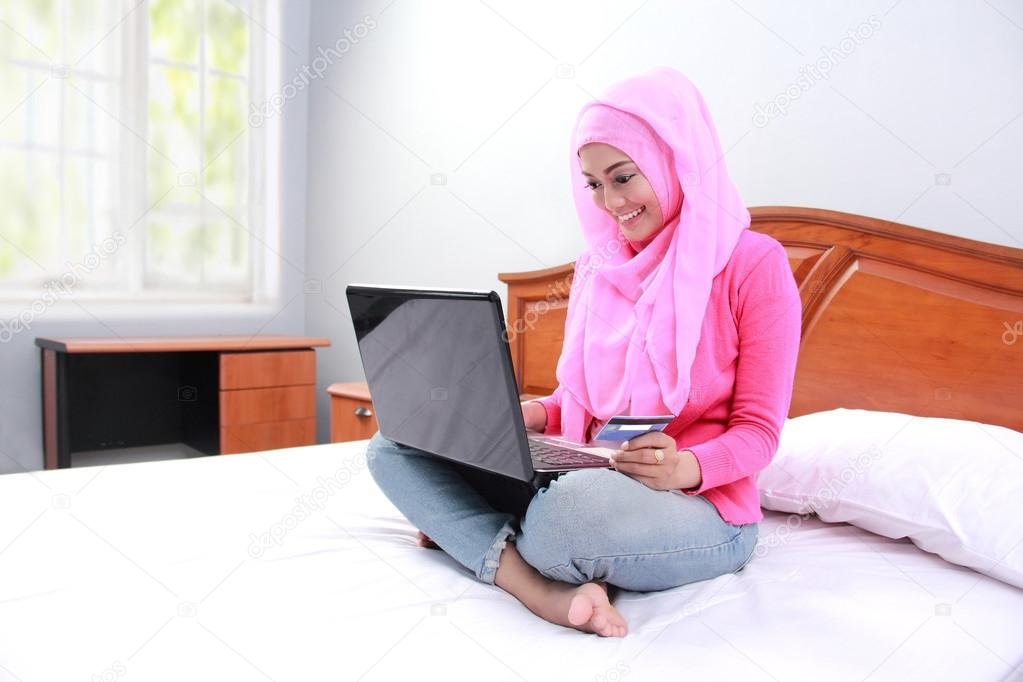 Young muslim woman work using laptop on bed