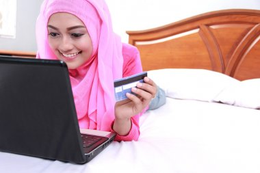 young muslim woman working on laptop