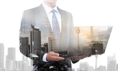 Double exposure of businessman using laptop computer