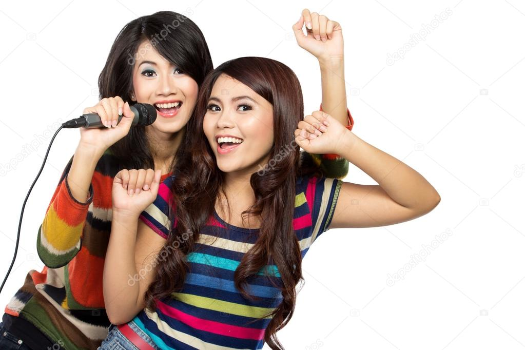 Two asian girls in striped t-shirt singing together