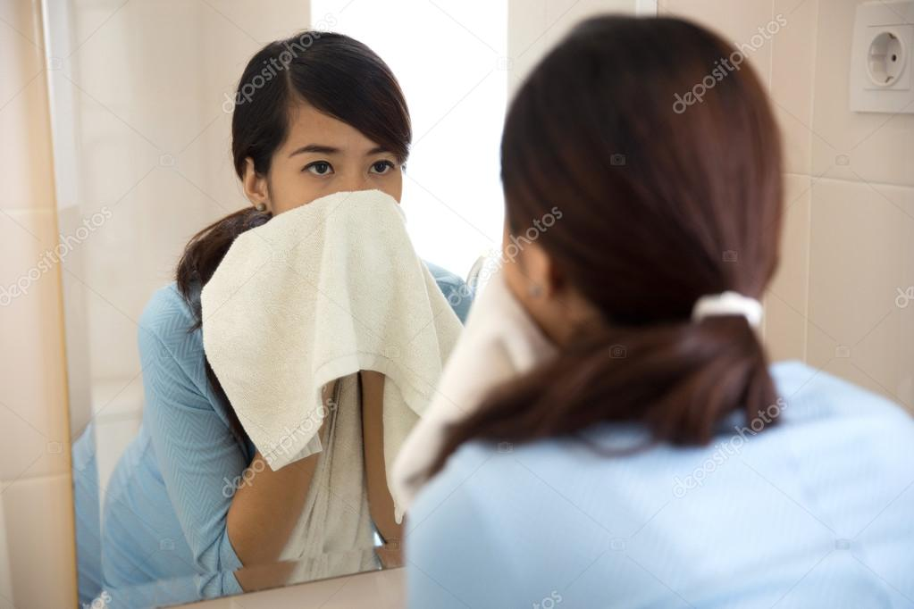 Beautiful asian woman wiping her face with towel, looking at mir