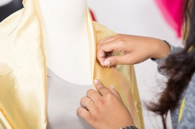 Young asian designer pinning a fabrice on a mannequin, close up