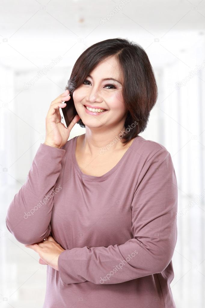 Pretty Asian middle aged Woman on the phone