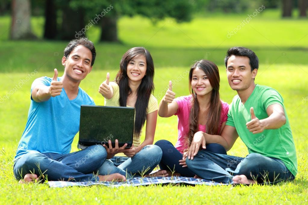Students studying in the park using laptop computer. thumb up a