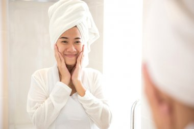 Young asian woman smile while looks at the mirror, happy