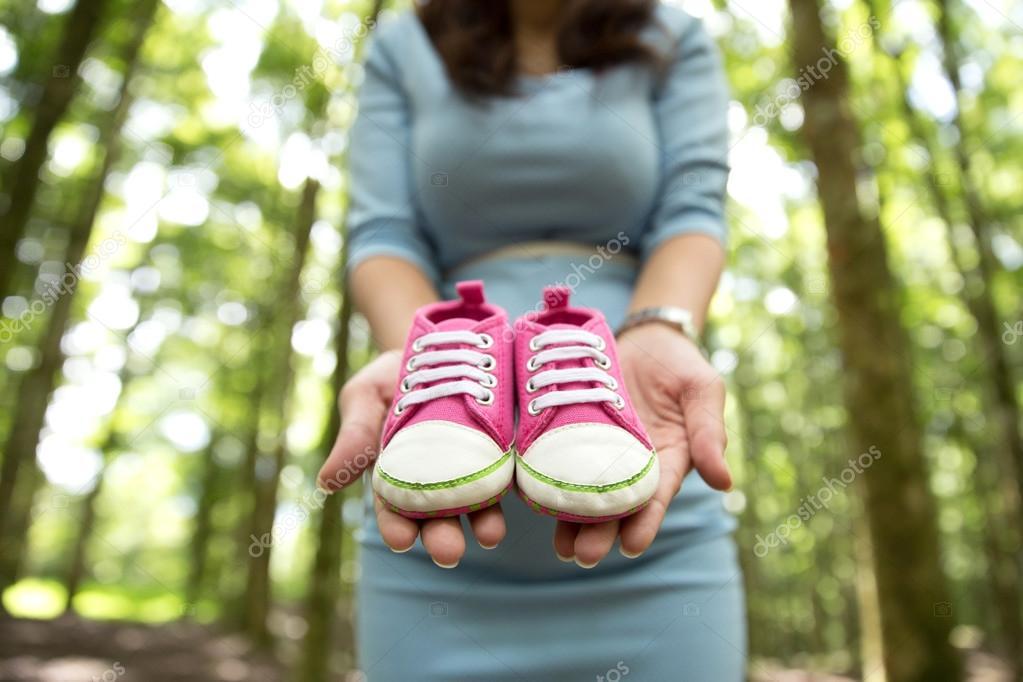 cfe92b2b110 Zwangere vrouw met een paar van roze sneakers peuter schoenen — Stockfoto