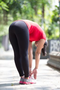 Asian woman doing stretching exercise during outdoor cross train