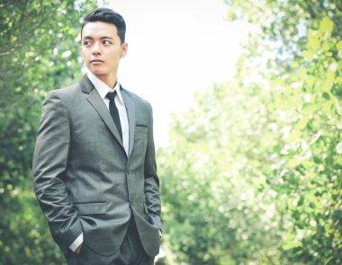 handsome groom with hands in pocket