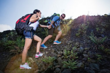 Mixed race couple go trekking together, walking on an uphill,  n