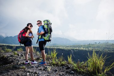 Mixed couple go trekking together, nature background