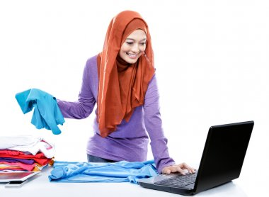 multitasking young woman wearing hijab folding clean clothes whi