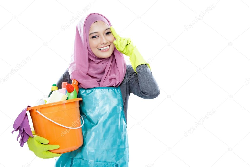 young woman wearing hijab holding a bucket full of cleaning supp