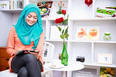 young muslim woman enjoy playing her tablet at decorated living