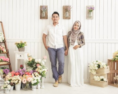 married couple standing and smiling at decorated room