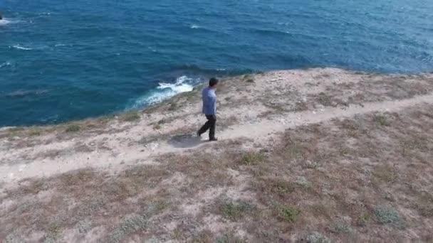 Young caucasian man walking away from the ocean