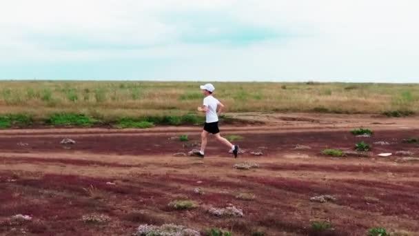 Boy runs a country road along the shore of the bay
