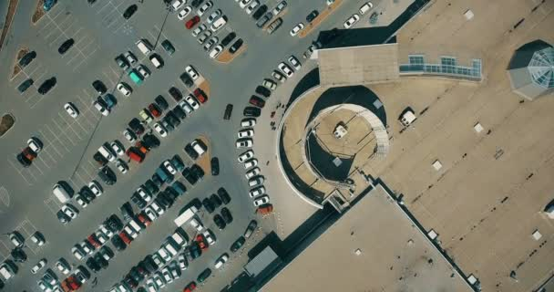 Aerial overlooking the parking with cars and people.