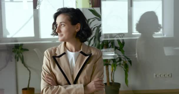Portrét šťastné spokojené mladé arabské kavkazské podnikatelky studentka na volné noze sedí v kanceláři odvrátit pohled v okně sen o budoucnosti, usmívající se hezká dívka profesionální pózování se zkříženými pažemi
