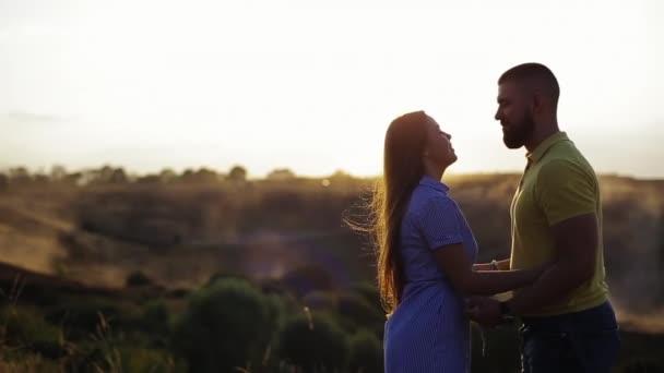 Közepes kilátás fiatal pár szerelmes szakállas srác és gyönyörű lány ölelés és csókolózás kihalt háttérben este, háttér naplemente lassított felvételen. Romantikus dátum a természetben együtt