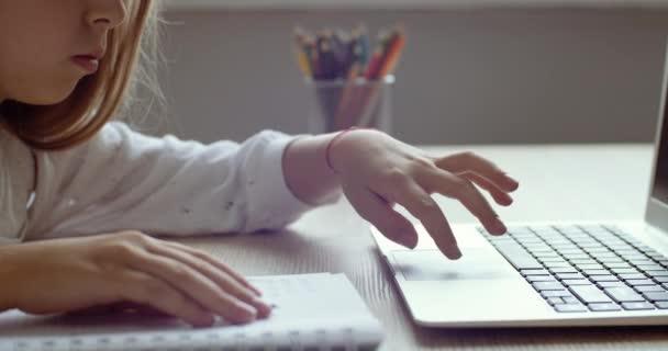 Schüler der Grundschule tippen in der Klasse mit kleinen Fingern auf der Tastatur eines Laptops am heimischen Schreibtisch. Fernunterricht für Mädchen während der Pandemie-Quarantäne