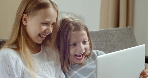 Two cute little preschool children friends girl laughing watching online cartoons video movie together, happy kids sisters learn use laptop computer sit on sofa at home, children technology concept