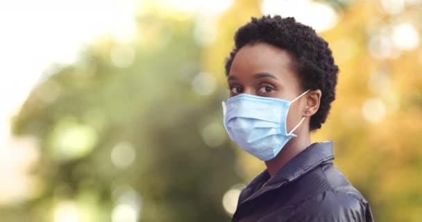 Patientin schwarze Frau krank auro amerikanisches Mädchen, das im Freien im Profil steht und in die Kamera blickt, trägt eine medizinische Schutzmaske auf dem Gesicht, dreht den Kopf weg und geht die Herbststraße entlang, Nahaufnahme