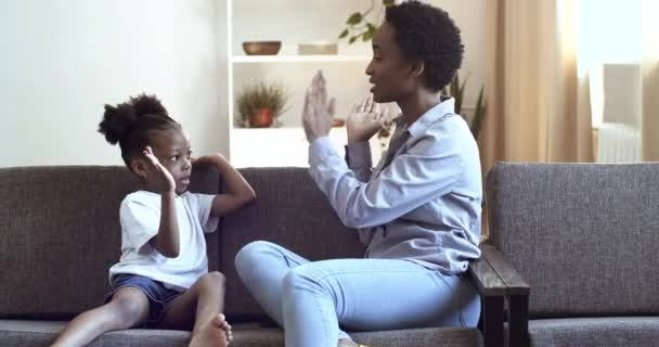 Mom and daughter of African ethnicity clap their hands sitting on sofa at home in living room. African woman and little black girl playing hands high five together while resting, motherhood concept