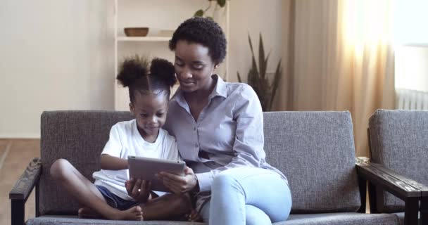 Šťastná rodina africký maminka a dcera baví pomocí digitální tablet sedí na gauči pohovka, etnické matky hlídání dětí s dívkou drží PC počítač při sledování obrazovky karikatury on-line