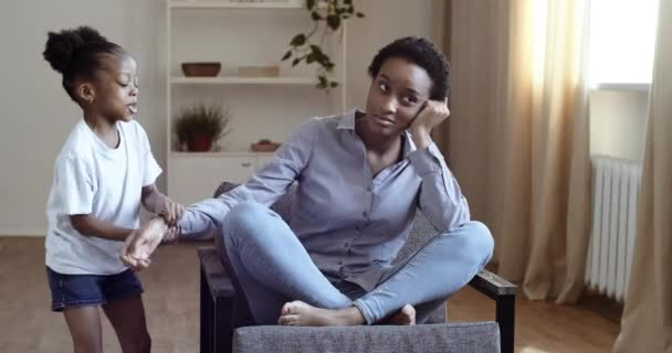 Young tired single african mother suffers from headache sitting on couch feeling stress while her daughter running around her shouting touching mom, black female babysitter exhausted by noisy kid girl