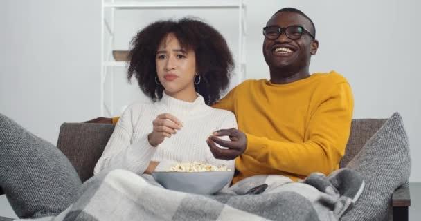 Afro-amerikai pár férfi és fiatal lány ül a kanapén TV-filmeket néz nő elégedetlen a program nem érti a férje nevet a komédia erők barátja váltani csatorna