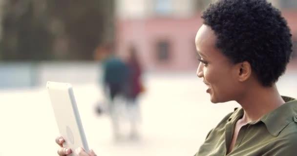 Junge afroamerikanische Studentin läuft durch die Stadt, nutzt digitale Tablet-Computer, um sich mit Familie oder Freunden im Ausland zu verbinden, spricht mit Webcam, Online-Konferenznetzwerk, Fernkommunikationskonzept