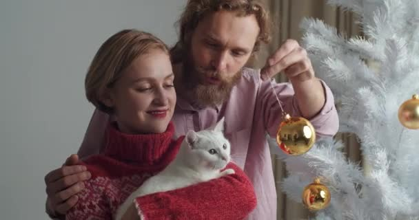 Close-up portrait caucasian couple young family wife and bearded husband holding white cat in their arms playing with beloved pet with Christmas ball decorations having fun at home spend time together