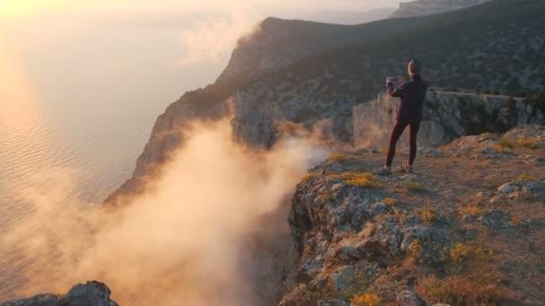 Kreisende Touristenmädchen, die über bunten Wolken am Rande des Berges über dem Meer stehen und mit dem Smartphone Fotos machen. Eine Frau an einer Klippe filmt den schönen Sonnenuntergang und die Verdunstung