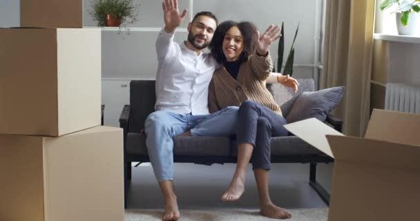 Multiethnic pár kudrnaté manželka a kavkazský manžel sedí na pohovce v obývacím pokoji v blízkosti lepenkových krabic doručena kurýrem odpočinek po přestěhování do nového domu nákup bytu dva majitelé domů mává ahoj