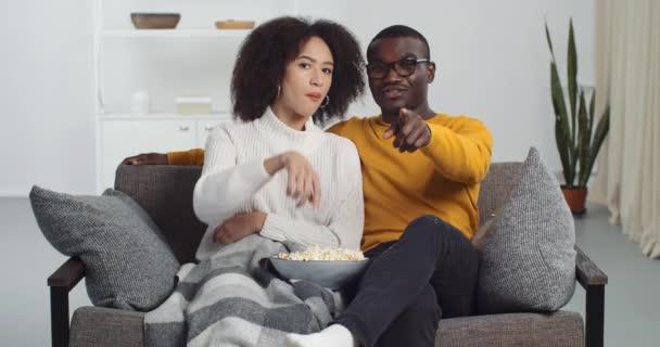 Boldog afro-amerikai pár fiatal család barát és barátnő töltenek időt együtt otthon ül kanapén néz filmeket TV műsorok pihen eszik popcorn ujjal mutogatva kamera mosolyog
