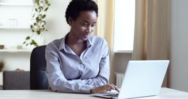 Afro americká studentka černošky obchodní žena sedí na pracovišti domácí kancelář při pohledu na obrazovce notebooku čte dobré zprávy pořady na kameře jako dává palce nahoru dělá gesto úspěchu schválení
