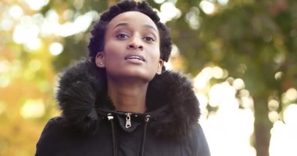 Afroamerikanische Mädchen schwarze Frau trägt Oberbekleidung guckt aus Freund Freund schaut in die Ferne auf der Suche nach vertrautem Gesicht winkende Hand zur Begrüßung Ratschläge, sich allein im Freien zu stellen