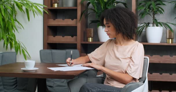 Portrait of Afro American girl with curly hair sits at wooden table holds document in her hands reads letter picks up pen writes on paper information report makes notes plans works in cafe restaurant