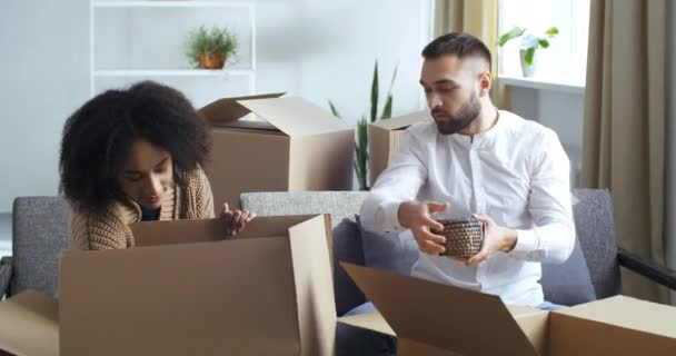 Two people curly haired afro american black mixed race girl and caucasian man unpacking cardboard boxes sorting things out in new house after moving, receiving delivery from courier looking at dishes