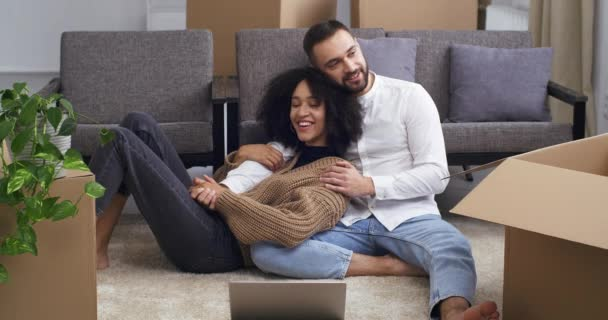 Tired young people african american curly woman and white caucasian man sit hugging on floor near cardboard boxes and houseplants rest after moving to new house apartment flat, buying real estate