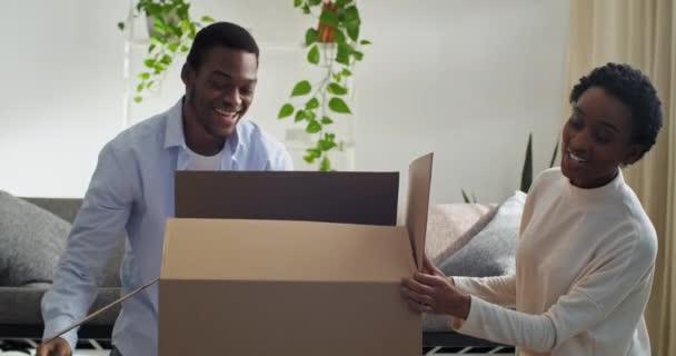 Afro americká dvojice manželka a manžel otevírá kartónovou krabici vypadá zvědavý dítě dcera holčička uvnitř balíčku se směje radostné předstírání, že koupil batole šťastný milující rodinný koncept