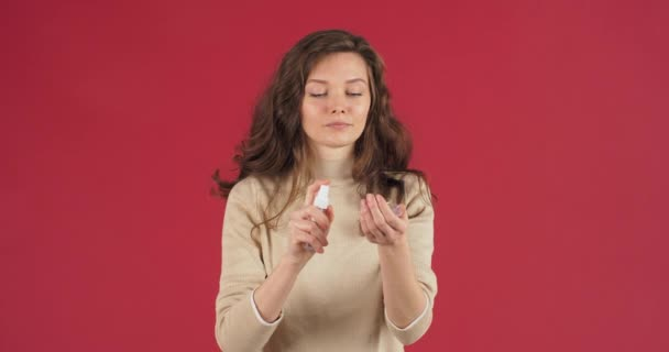 Responsible girl caucasian woman female student model stands posing on red studio background sprinkles with alcohol antibacterial spray gel sanitizer handles washes hands palms from bacteria microbes