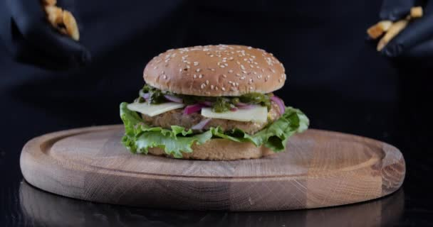 Zpomalený film zblízka oříznuté semeno mužské ruce v černých rukavicích rozložit hranolky na dřevěné desce vedle vydatný obrovský chutný burger, samec šéfkuchař připravuje rychlé občerstvení servírovat jídlo servírované v baru restaurace