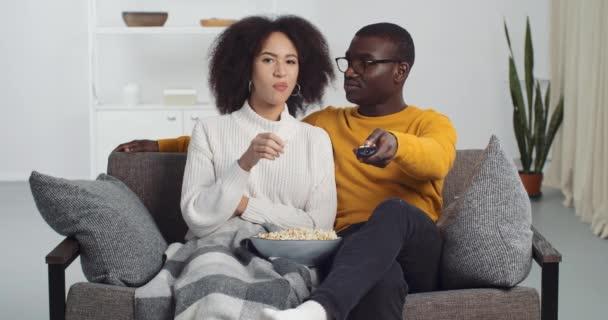 Vegyes verseny lány és fekete férfi szemüvegben barát és barátnő tévézni együtt ül otthon a kanapén élvezi finom popcorn választotta film, srác csatornát vált távirányítóval