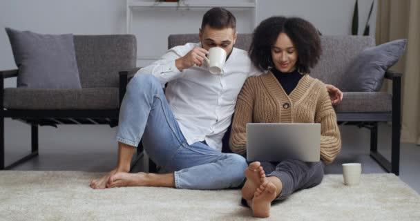 Mezirasový pár se dívá na notebook moderního počítače, manželka manžel používá technologie pro on-line nakupování nebo komunikaci, zatímco sedí doma na podlaze, pije čaj nebo kávu z bílých pohárů